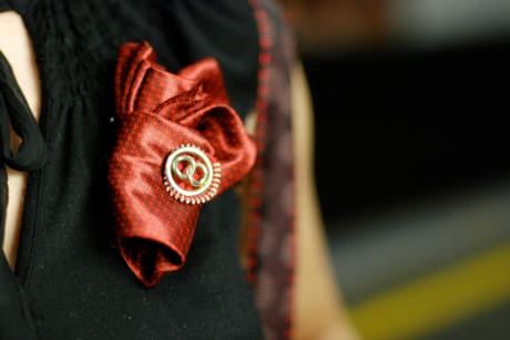 The headless Steph wearing a red rolled tie and zipper broach