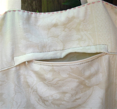 The flipside of the bag is made from reclaimed cream damask and the lining from a soft minty cashmere scarf.